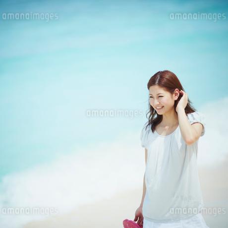 砂浜を歩く女性の写真素材 [FYI02053262]