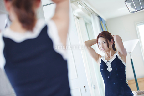 鏡に向かい髪を結う女性の写真素材 [FYI02053289]