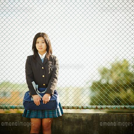 フェンスに寄りかかる女子学生の写真素材 [FYI02053302]