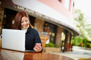 オープンカフェでスマートフォンとノートパソコンを操作する女性の写真素材 [FYI02053304]