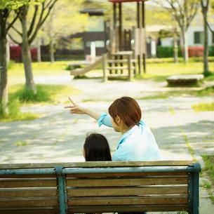 公園のベンチに座る母と子の後姿の写真素材 [FYI02053345]
