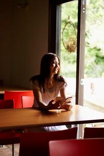 本を持ち窓の外を眺める女性の写真素材 [FYI02053380]