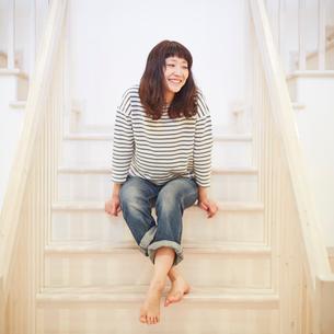 階段に座る若い女性の写真素材 [FYI02053393]