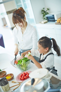 料理をする女の子と母親の写真素材 [FYI02053426]