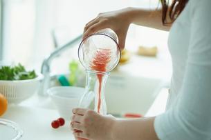 トマトジュースを作る女性の写真素材 [FYI02053433]