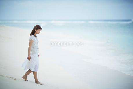 砂浜を歩く女性の写真素材 [FYI02053461]
