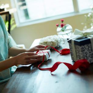 ギフトボックスにリボンをかける女性の手元の写真素材 [FYI02053468]
