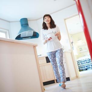 鍋を持って歩く若い女性の写真素材 [FYI02053502]