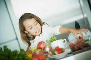 キッチンでイチゴをつまむ女の子の写真素材 [FYI02053518]