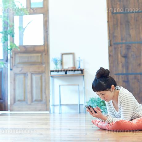 床に寝そべりスマートフォンを操作する若い女性の写真素材 [FYI02053538]