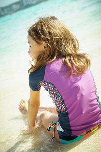 波打ち際に座る女の子の写真素材 [FYI02053547]