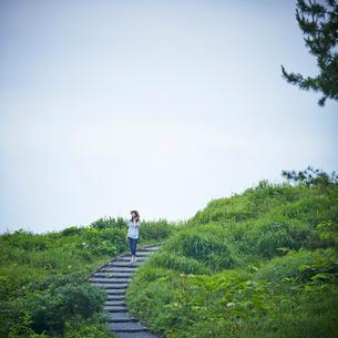 緑の野原と階段の道を歩く女性の写真素材 [FYI02053559]