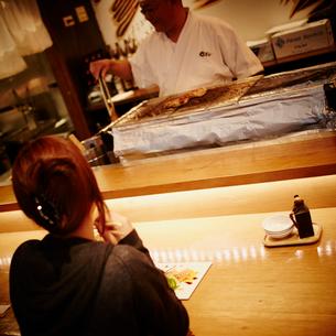 カウンターで向い合う料理人と女性客の写真素材 [FYI02053629]