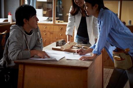 作業場で打ち合わせをする3人の若者達の写真素材 [FYI02053661]