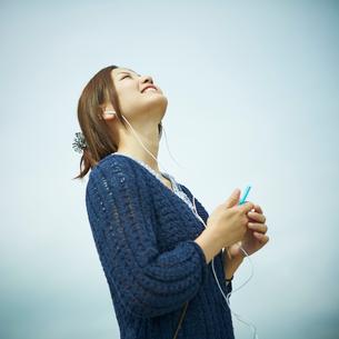 音楽を聴く女性と青空の写真素材 [FYI02053676]