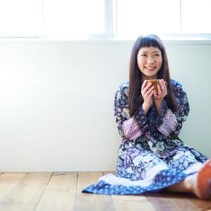 床に座りコーヒーカップを持つ若い女性の写真素材 [FYI02053686]