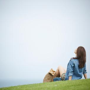 芝生の上に座る女性の後ろ姿の写真素材 [FYI02053736]