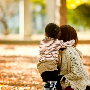 秋の公園で寄り添う女の子と母親の写真素材 [FYI02053759]