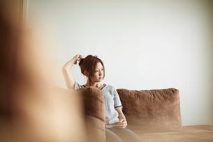 ソファに座り髪に触れる女性の写真素材 [FYI02053777]