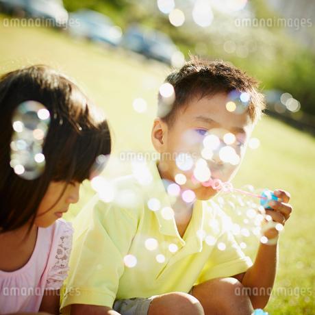 シャボン玉で遊ぶ男の子と女の子の写真素材 [FYI02053809]
