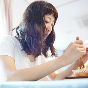 マフィンを食べる若い女性の写真素材 [FYI02053828]