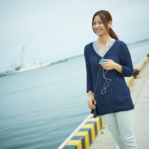 音楽を聴きながら港を歩く女性の写真素材 [FYI02053875]
