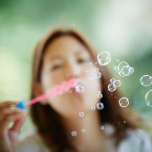 シャボン玉を吹く女性の写真素材 [FYI02053898]