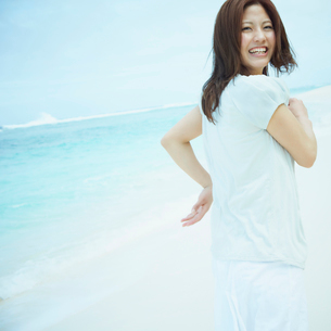 振り向く笑顔の女性と海の写真素材 [FYI02053904]