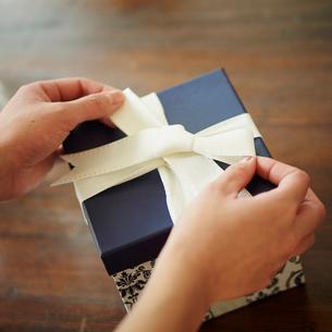ギフトボックスにリボンを結ぶ女性の手元の写真素材 [FYI02053909]