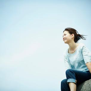 防波堤に座る女性と青空の写真素材 [FYI02053915]