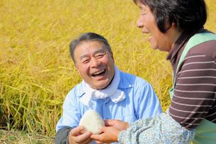 稲田でおにぎりを持つ農家の夫婦の写真素材 [FYI02053946]