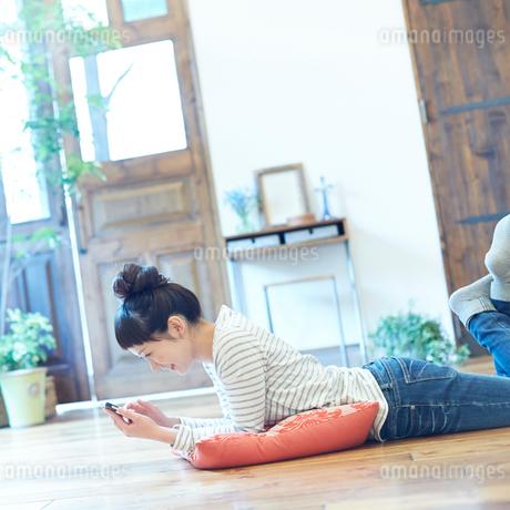 床に寝そべりスマートフォンを操作する若い女性の写真素材 [FYI02053997]