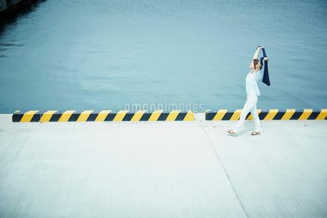 伸びをしながら港を歩く女性の写真素材 [FYI02054023]