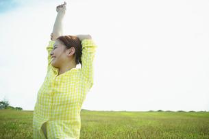芝生の上に座り伸びをする女性の写真素材 [FYI02054086]