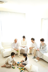 積木で遊ぶ子供達とソファに座る両親と祖父母の写真素材 [FYI02054130]