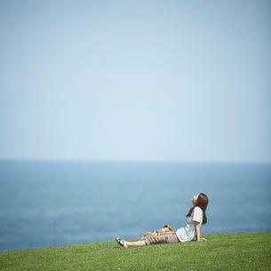 芝生の上に座る女性と海の写真素材 [FYI02054138]
