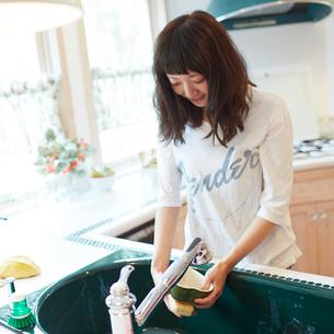 キッチンで洗い物をする若い女性の写真素材 [FYI02054216]