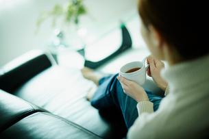 コーヒーカップを持ってソファに座る女性の後姿の写真素材 [FYI02054254]