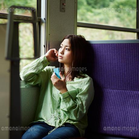 列車の中で音楽を聴く女性の写真素材 [FYI02054266]