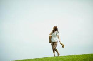 芝生の上を歩く女性の写真素材 [FYI02054299]