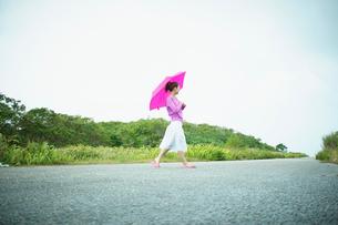傘をさして歩く女性の写真素材 [FYI02054308]