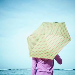 傘をさして海を眺める女性の後姿の写真素材 [FYI02054323]