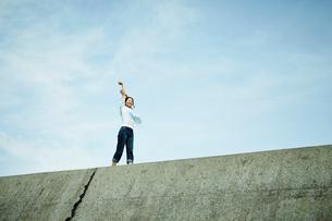 防波堤の上で伸びをする女性の写真素材 [FYI02054327]