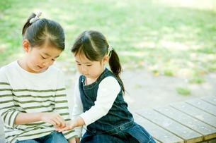ベンチに座る2人の女の子の写真素材 [FYI02054339]