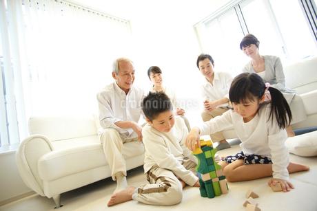 積木で遊ぶ子供達とソファに座る両親と祖父母の写真素材 [FYI02054400]