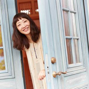 ドアを開ける若い女性の写真素材 [FYI02054407]