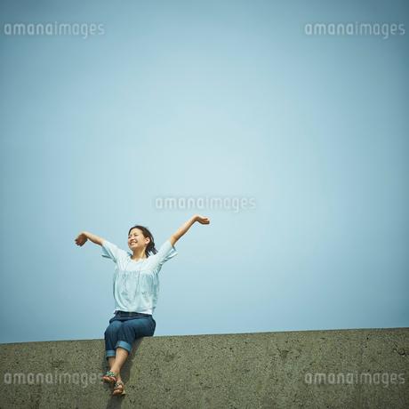 伸びをする女性と青空の写真素材 [FYI02054413]