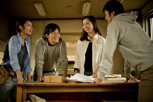 作業場で打ち合わせをする4人の若者達の写真素材 [FYI02054414]