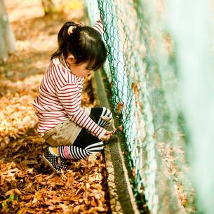 フェンスの側にしゃがむ女の子の写真素材 [FYI02054423]