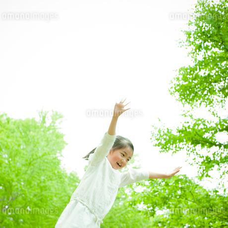 両手を上げる女の子と新緑の写真素材 [FYI02054435]